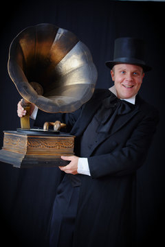 Actor in a black hat and a suit of the 19th century holding a gramophone