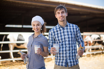 country couple of farmers posing with glass of milk at cowfarm