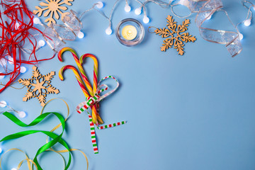 Christmas blue background with candy canes, candle and decorations
