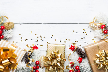 Heap of gifts or presents boxes, snowy fir tree and Christmas decorations on white wooden table top view. Flat lay.