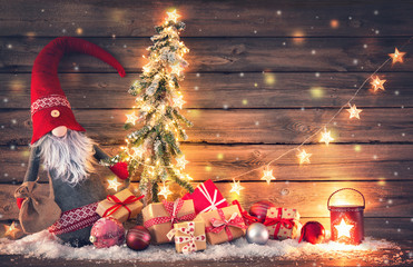 Santa Claus or dwarf holds a fir tree with Christmas lights surrounded by gift boxes and glowing lantern