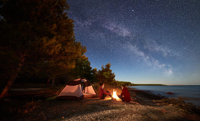 Fototapeten Camping Night camping on shore. Man and woman hikers having a rest in front of tent at campfire under evening sky full of stars and Milky way on blue water and forest background. Outdoor lifestyle concept