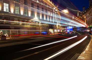night scene of London city United Kingdom with the moving red buses and cars - long exposure photography