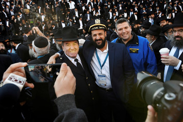 NYPD Chief Scholl switches hats with a rabbi as they pose for a picture, as rabbis from around the world gathered for a group photo in front of the Chabad-Lubavitch world headquarters in the Brooklyn borough of New York