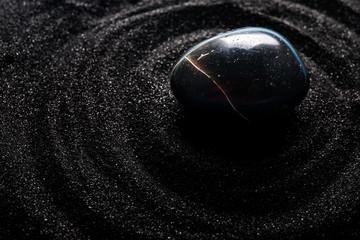 zen stones on black sand background.   equilibrium, zen stone and sand background, relaxation.