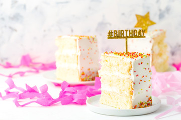Slice of birthday cake and pink paper decoration, copy space