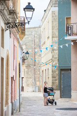Presicce, Apulia - A woman wheeling her stroller through the old town