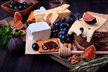 Assortment of appetizers: different sorts of cheese, crackers, grapes, nuts, olive marmalade, figs and olives against the dark background