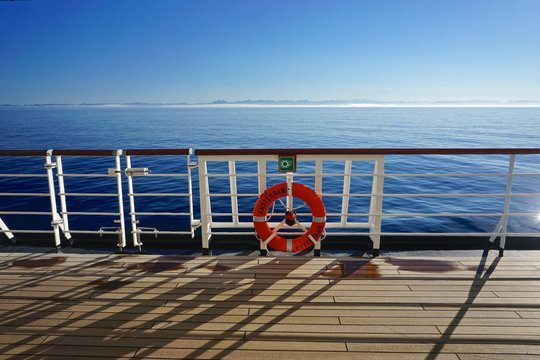 Morning at sea en route to Alaska from Seattle. Scene on the deck of a cruise ship with mountains in the background.