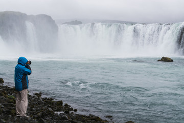 Photographer taking picture of Godafoss waterfall, Iceland