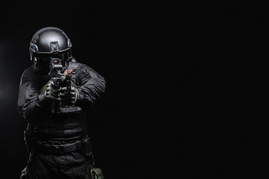 Airsoft player in an outfit with weapons on a black background