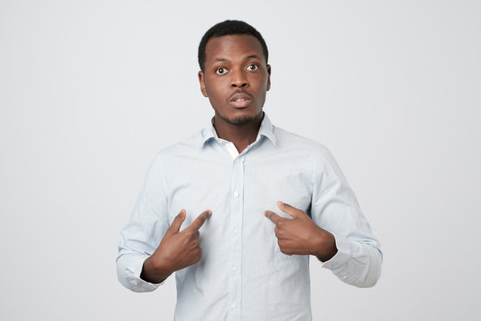 Young african man pointing at himself, making excuses or verbally defending,