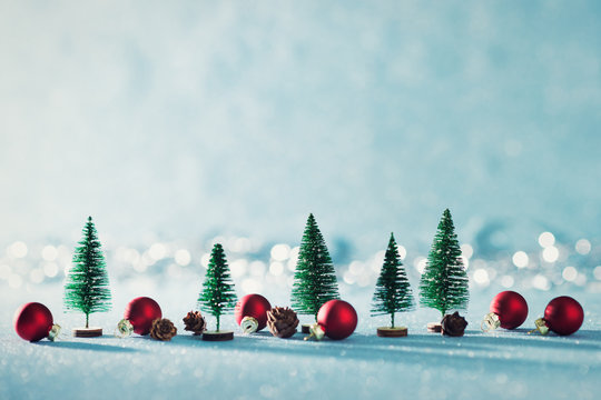 Magical miniature winter wonderland background. Evergreen trees, pine cones and red christmas baubles on shiny blue background with bokeh in the background.