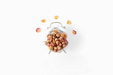 Creative idea dry rose buds alarm clock white background top view flat lay