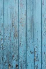 Peeling blue paint on decaying wood panel fence/door