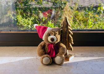 niedlicher Teddy mit Weihnachtsmütze auf der Fensterbank