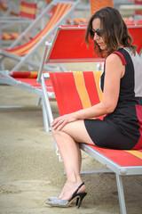 donna sulla spiaggia con tacchi alti
