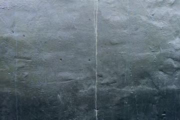 Black shiny painted wall, roughly rendered, drips running down