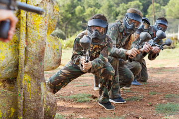 Paintball team running with marker guns