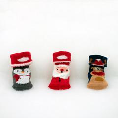 niedliche Babysocken mit Weihnachtsmotiv auf weißem Vlies