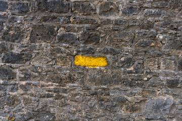 Old grey stone wall with one stone highlighted painted bright yellow