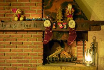 Rustikaler Kamin mit Weihnachtsdekorationen, Weihnachtsstrümpfen und Petroleumlampe.