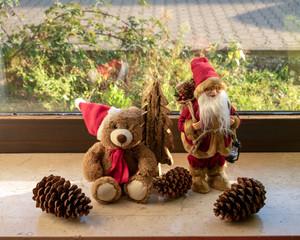 Weihnachts-Teddy und Weihnachtsmann mit Dekorationen auf der Fensterbank