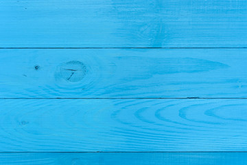 An old wooden wall painted with turquoise paint, in the holes of the hole a bitch