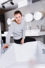 Portrait of woman buyer choosing ceramic bath  in shop