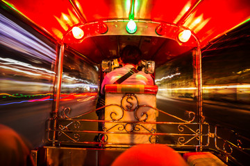 view from inside a Tuk Tuk vehicle with moving trffice light at night in Bangkok, Thailand