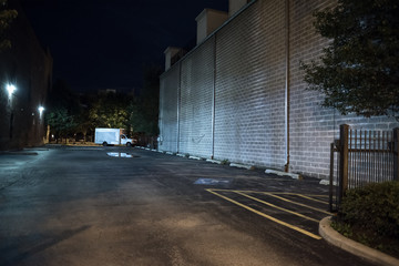 Fotomurales - Dark and scary empty downtown urban city parking lot with a spooky van truck next to a large brick wall at night