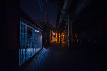 Fototapete - Dark and scary downtown urban city street alley under an eerie vintage industrial railroad subway bridge with an illuminated gate fence at night