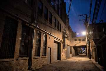 Fototapete - Dark and scary downtown urban city street alley scene with an eerie vintage industrial warehouse factory skyway at night