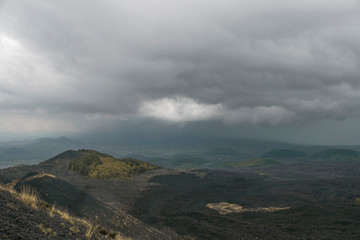 Mount Etna landscape with old volcano craters in cloudy rainy day in September in Sicily, Italy