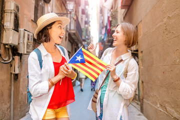Two Happy woman tourists having fun and travel with catalan flag near the Cathedral in Barcelona city