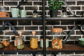 Black loft style storage stand with ceramic and wooden dishware in kitchen. Brick wall background