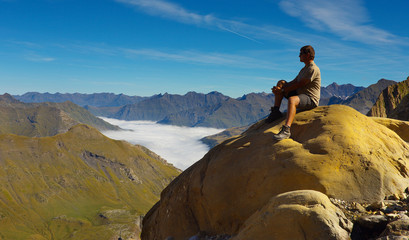 Resting tourist on the stone with mountains on backround, Pyrenees