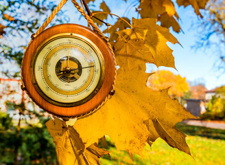 Old barometer, autumnal leaves are on textured wooden surface  Concept of forecasting. Translations from German to English are: sturm is storm; veranderlich is changeable; schone is enjoyable