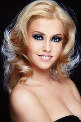 Young beautiful smiling woman with blonde curly hair and sparkly smoky eye make-up