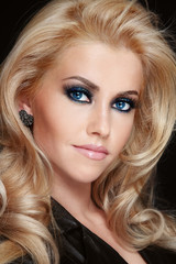 Young beautiful woman with blonde curly hair and sparkly smoky eye make-up