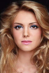Young beautiful woman with fancy cat eye make-up and long curly hair