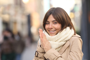 Happy woman being cold in the street in winter