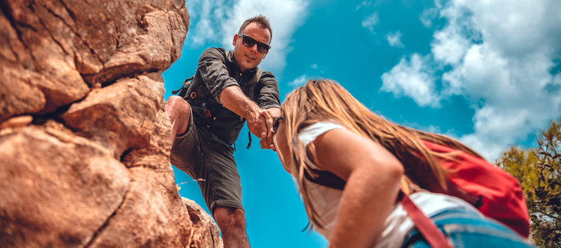 Father and daughter climbing on cliff