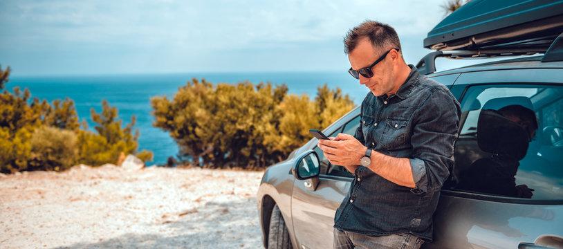 Man lean on car using smart phone
