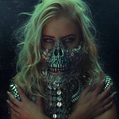 beautiful blonde woman with intense look wearing a silver mask with skull and metal pieces, halloween