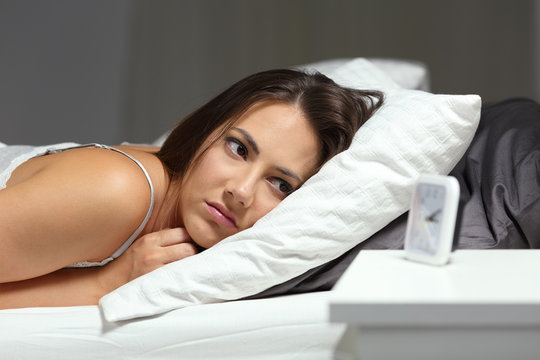 Sleepless insomniac girl looking at alarm clock in the night
