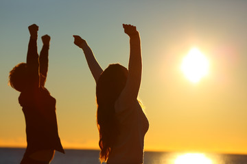 Excited friends raising arms at sunset on the beach
