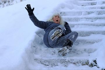 Eine Frau ist auf einer schneeglatten Treppe ausgerutscht und hingefallen