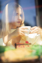 Beautiful blonde model spending time in the restaurant with a cup of coffee. Shot through window glass