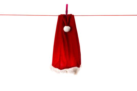 Un chapeau de père noël rouge suspendu à un fil rouge sur fond blanc